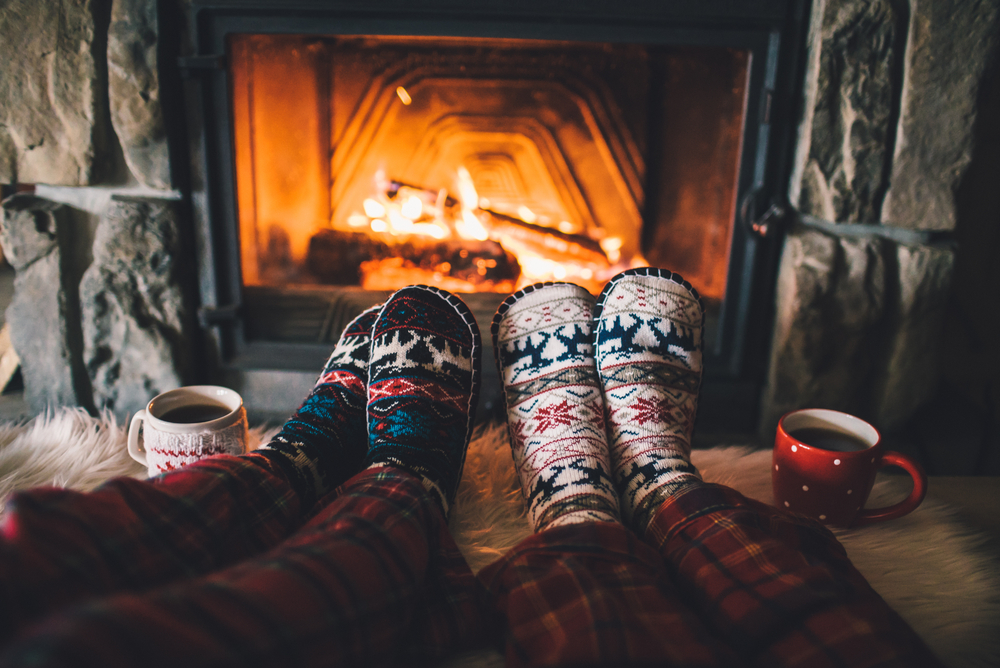 A Phoenix couple warm their feet by the fire while wearing patterned Christmas socks