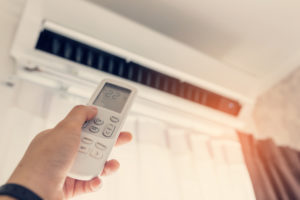Woman changes her air conditioning unit with a remote